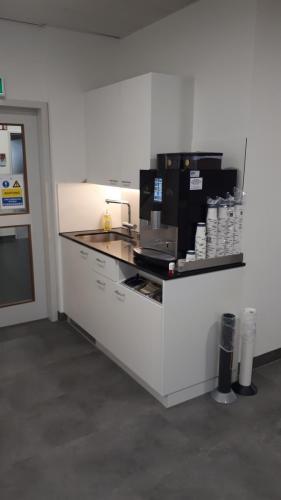 Kaffeeküche mit Steinabdeckung mit Gerätenund Behälter für Zubehör