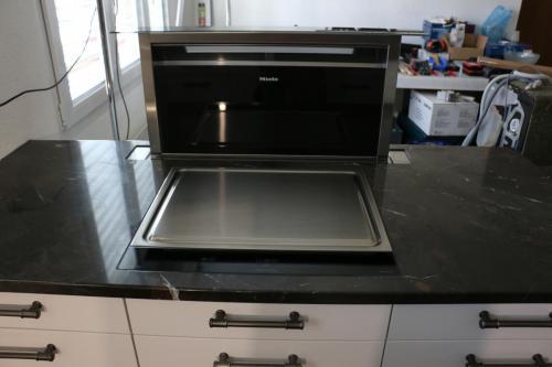Küche HochglanzInsel mit GrillDunstabzug in Stein integriert
